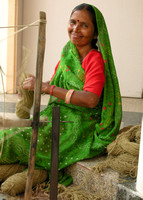 Woman spins yarn for weaving rugs, Jaipur, India.